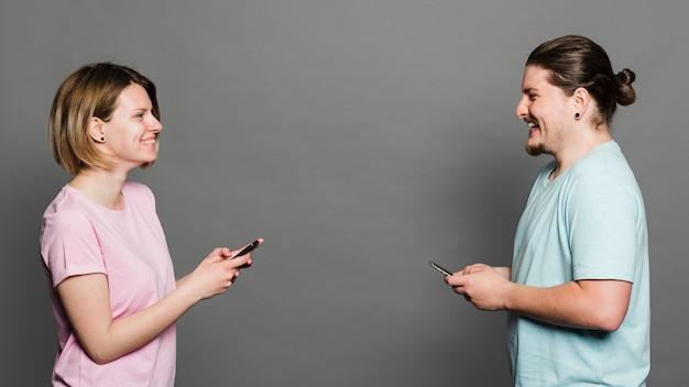 Sorrindo, retrato, de, par jovem, ficar, contra, parede cinza, usando, telefone móvel