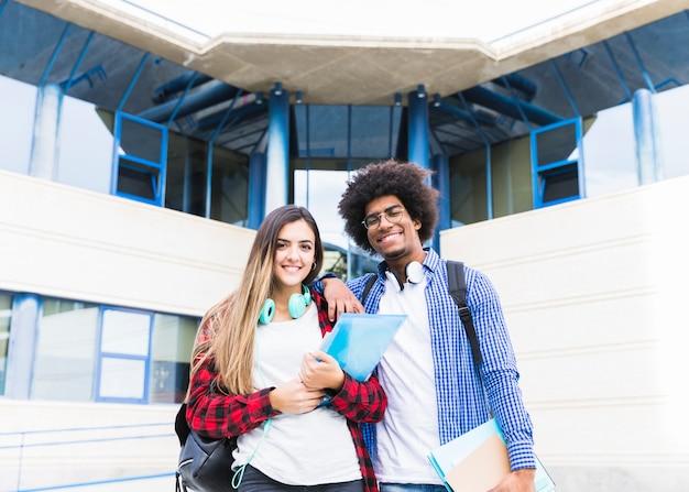 Sorrindo, retrato, de, par jovem, segurando, livros, em, mão, ficar, frente, universidade, predios, olhando câmera