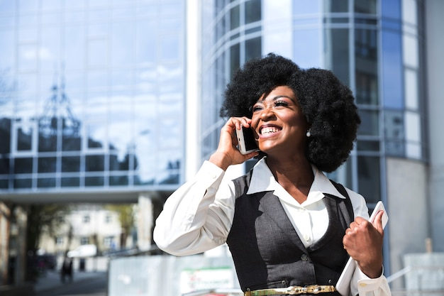 Sorrindo, retrato, de, um, confiante, jovem, executiva, segurando, tablete digital, falando telefone móvel