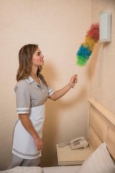 Sorrindo, retrato, de, um, jovem, empregada, limpeza, a, parede, luz, com, coloridos, macio, espanador