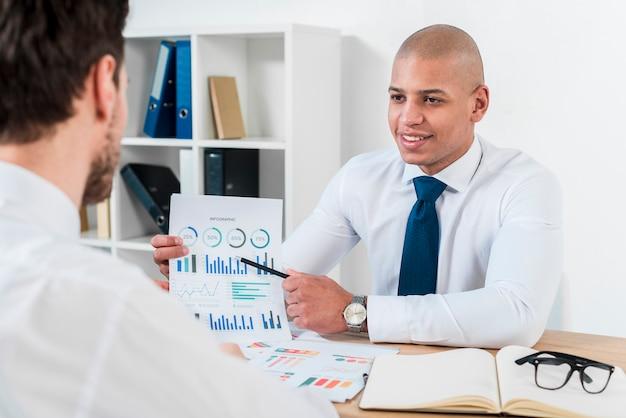 Sorrindo, retrato, de, um, jovem, homem negócios, discutir, a, gráfico, com, seu, colega, em, local trabalho