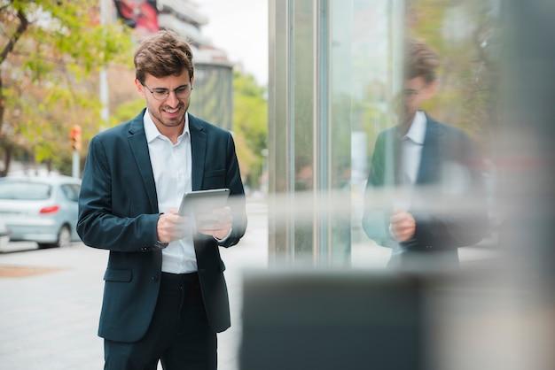 Sorrindo, retrato, de, um, jovem, homem negócios, usando, tablete digital, ao ar livre