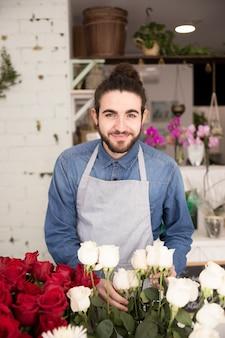 Sorrindo, retrato, de, um, jovem, macho, florista, segurando, flores brancas, em, mão