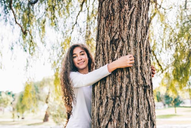Sorrindo, retrato, de, um, menina, abraçando, tronco árvore, parque