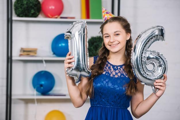 Sorrindo, retrato, de, um, menina aniversário, segurando, numeral, 16, folha, prata, balloon