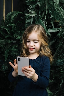 Sorrindo, retrato, de, um, menina, ficar, contra, frente, plantas, usando, telefone móvel