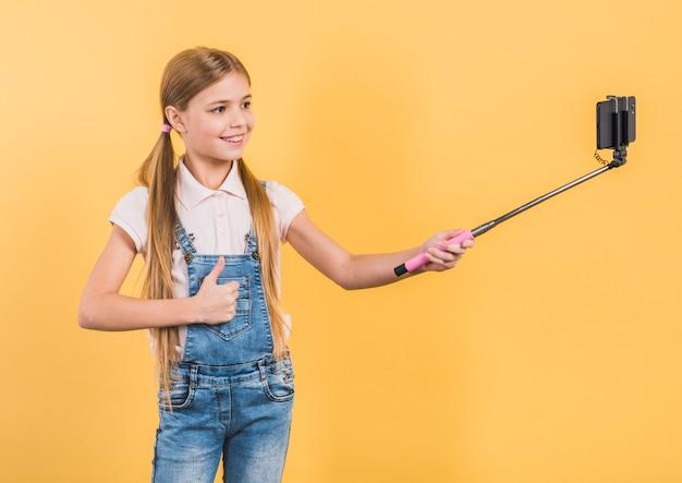 Sorrindo, retrato, de, um, menina, mostrando, polegar cima, sinal, levando, selfie, com, vara móvel, contra, fundo amarelo