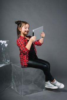 Sorrindo, retrato, de, um, menina sentando, ligado, translúcido, bloco, olhar, tablete digital