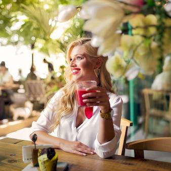 Sorrindo, retrato, de, um, mulher jovem, segurando, vidro suco, em, a, restaurante