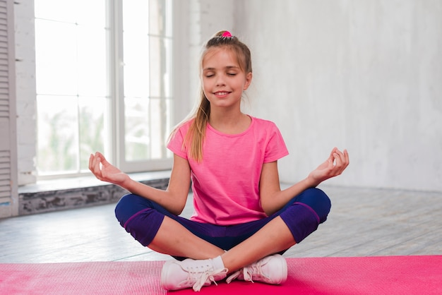 Sorrindo, retrato, de, um, mulher jovem, sentando, ligado, tapete cor-de-rosa, fazendo, meditação