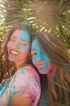 Sorrindo, retrato, de, um, mulheres jovens, com, holi, cor, ligado, seu, rosto, olhando câmera