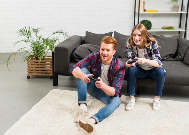 Sorrindo, retrato, de, um, par jovem, jogando videogame, em, a, sala de estar