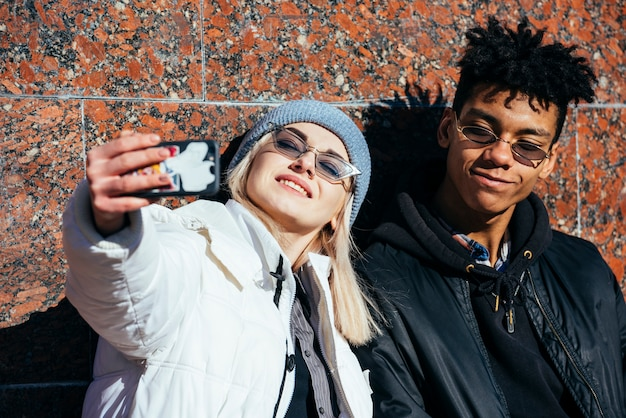 Sorrindo, retrato, de, um, par jovem, levando, selfie, ligado, telefone móvel