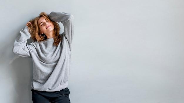 Sorrindo, retrato, jovem, mulher, contra, cinzento, parede