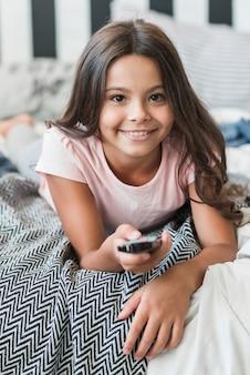 Sorrindo, retrato menina, mentindo cama, usando, controle remoto