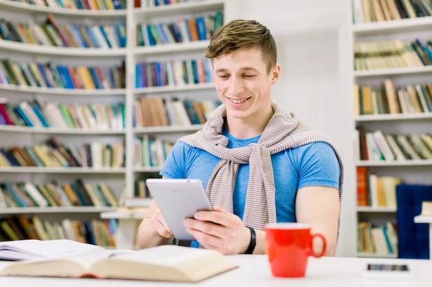 Sorrindo satisfeito jovem estudante do sexo masculino sentado na biblioteca e pesquisando informações no ipad durante a preparação para o teste