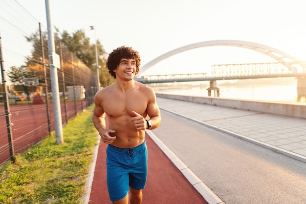 Sorrindo sem camisa homem desportivo correndo na pista de corrida perto do rio pela manhã