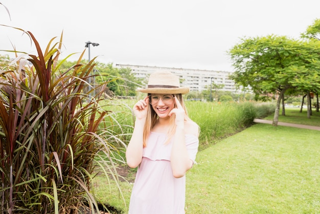Sorrindo, senhora, em, óculos, e, chapéu, perto, grama alta, em, parque