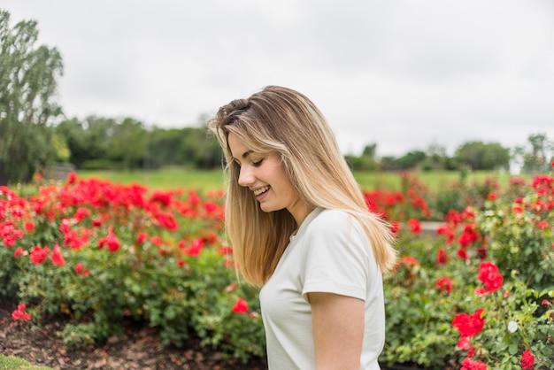 Sorrindo, senhora, em, t-shirt, perto, flores vermelhas