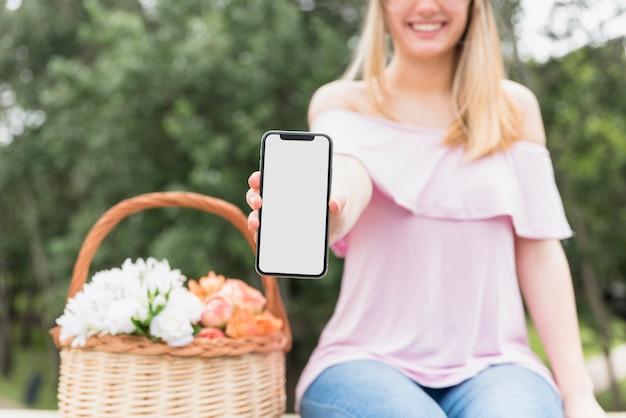 Sorrindo, senhora, mostrando, telefone móvel, perto, flores