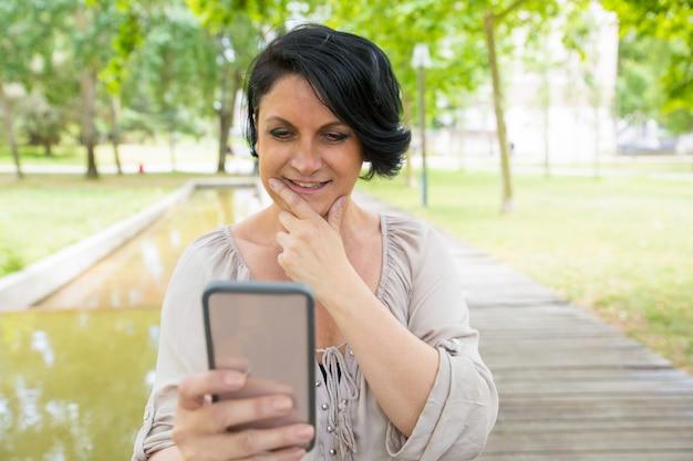 Sorrindo senhora pensativa tirando fotos no smartphone