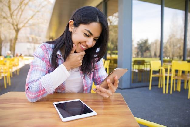 Sorrindo, senhora, usando, tabuleta, e, smartphone, em, café ao ar livre