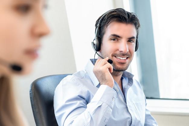 Sorrindo simpático homem hispânico, trabalhando em call center
