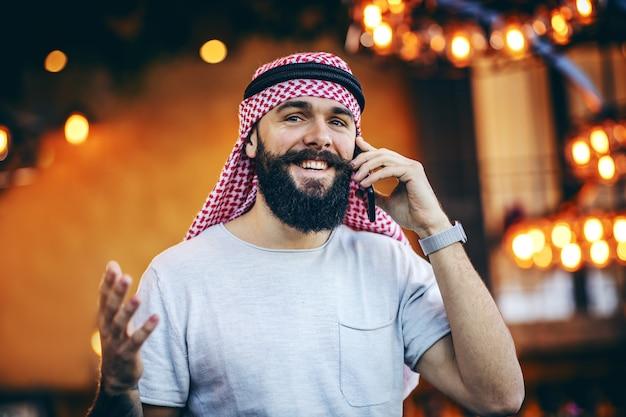 Sorrindo tatuado barbudo na moda muçulmano sentado no café pela manhã e tendo uma conversa de camponês com seu amigo no celular.