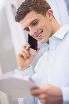 Sorrindo técnico ligando e lendo um documento