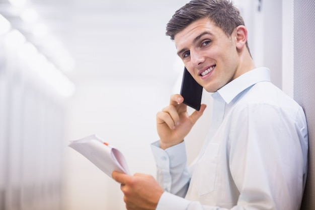 Sorrindo técnico no telefone, segurando um documento