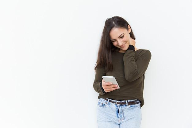 Sorrindo tímida linda mulher latina lendo a mensagem