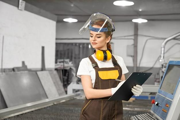 Sorrindo trabalhadora de fábrica de metal, escrevendo dados
