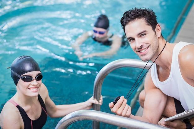 Sorrindo, treinador, mostrando, cronômetro, em, nadador, em, a, lazer, centro