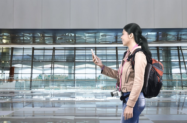 Sorrindo, turista asiático, mulher, com, mochila, usando, cellphone