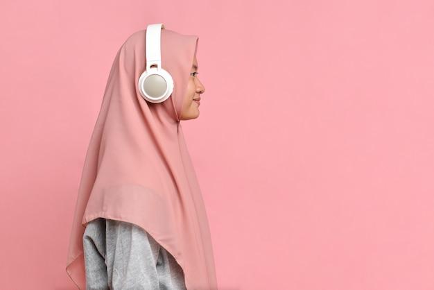 Sorrindo, uma jovem muçulmana em pé com fones de ouvido, vista lateral isolada em um fundo rosa