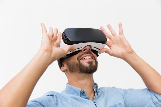 Sorrindo usuário masculino usando óculos vr, dispositivo de ajuste