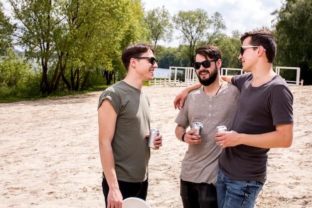 Sorrindo velhos amigos conversando na praia