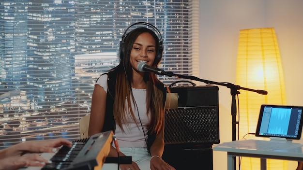 Sorrindo vocalista preta na música de fone de ouvido cantando no microfone no estúdio de gravação em casa