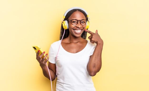 Sorrir com confiança apontando para o próprio sorriso largo, atitude positiva, relaxada e satisfeita e ouvindo música