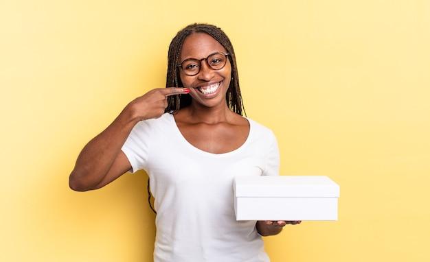 Sorrir com confiança apontando para o próprio sorriso largo, atitude positiva, relaxada e satisfeita e segurando uma caixa vazia