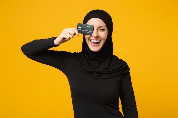 Sorrir divertida jovem árabe muçulmana em roupas pretas de hijab segurar na mão o cartão de crédito isolado no retrato de parede amarela. conceito de estilo de vida religioso de pessoas.