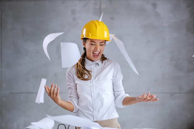 Sorrir e animado arquiteto feminino com capacete na cabeça terminou seu trabalho a tempo.