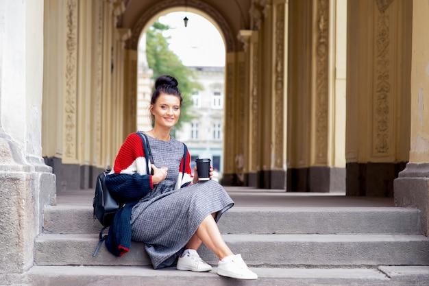 Sorrir estudante mulher adulta está sentado na escada.
