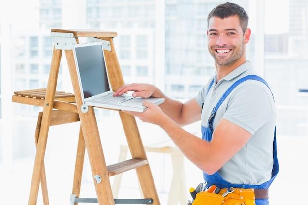Sorrir faz-tudo usando laptop pela escada no escritório