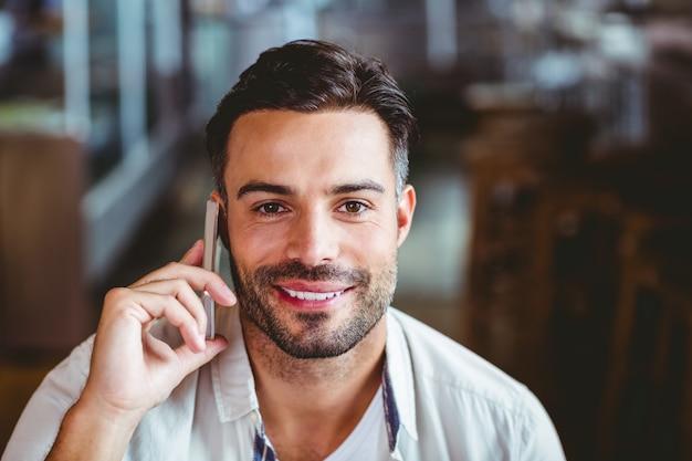 Sorrir homem ao telefone tomando café