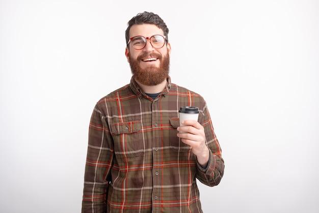 Sorrir homem barbudo está apreciando seu café da manhã para ir no fundo branco.