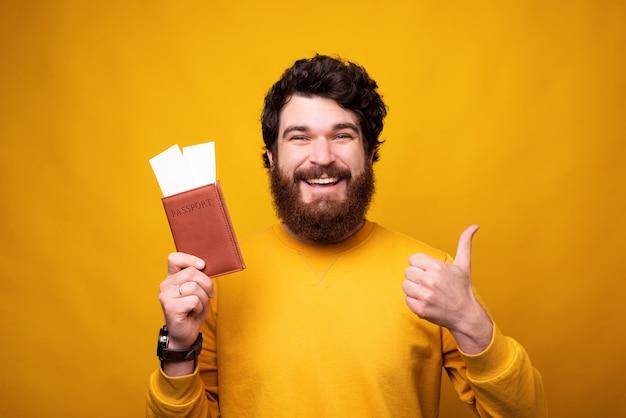 Sorrir homem barbudo está segurando um passaporte e bilhetes enquanto aparecendo o polegar.