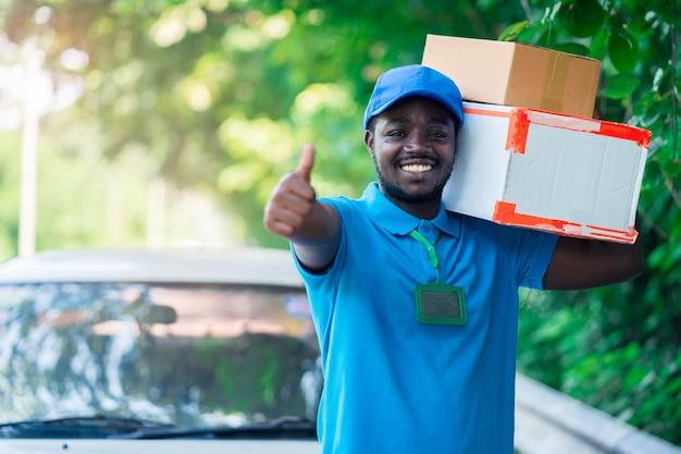Sorrir homem de correio postal entrega africana na frente do carro, entregando o pacote