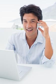 Sorrir homem usando seu laptop e falando no telefone