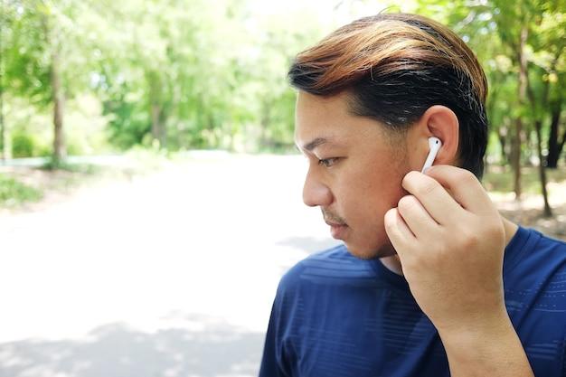 Sorrir jovem asiático em roupas esportivas está correndo ou correndo e ouvindo música com fones de ouvido brancos no jardim.